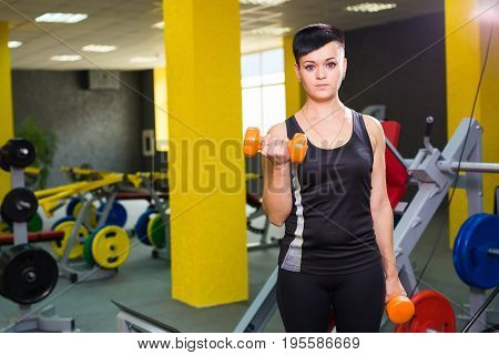 Beautiful fitness woman with lifting dumbbells . Sporty girl with short hair showing her well trained body