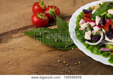 Fresh salad with chicken breast radish cucumber tomato onion bell pepper basil mint and other spices on old rustic wooden table. Copy space. Healhy eating