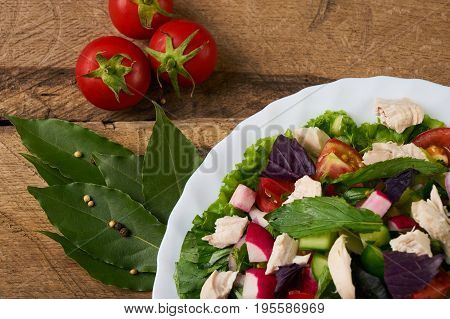 Fresh salad with chicken breast radish cucumber tomato onion bell pepper basil mint and other spices on old rustic wooden table. Copy space. Healhy eating. Top view