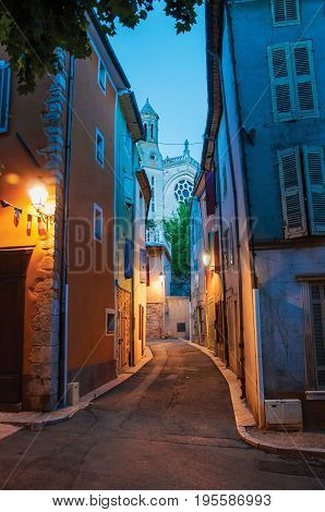 View of narrow alley and church in the early evening with lamp lit, in the lovely village of Rians. Located in Var department, Provence region, in southeastern France.