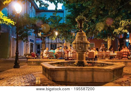 Rians, France - July 08, 2016. People dining in a square restaurant in the early evening, at the lovely village of Rians. Located in Var department, Provence region, in southeastern France.