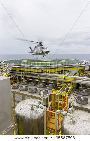 Aviation transportation. View of commercial helicopter depart after taking offshore passengers on oil and gas platform with foreground of process area.