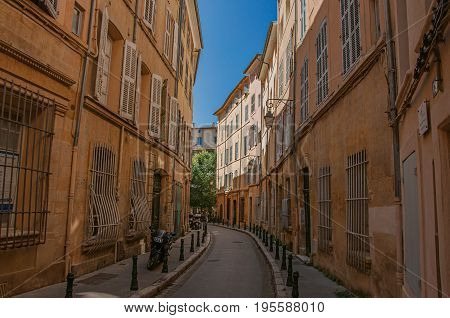 Aix-en-Provence, France - July 09, 2016. Narrow alley with buildings in the shadow in Aix-en-Provence, a pleasant and lively town in the countryside. Provence region, southeastern France