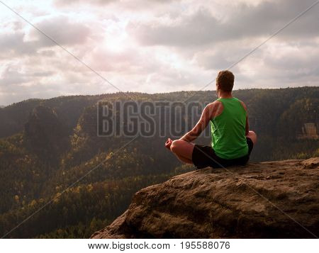 Man Meditating In Lotus Pose On Rocky Cliff. Sportsman Practicing Yoga On Stone Edge