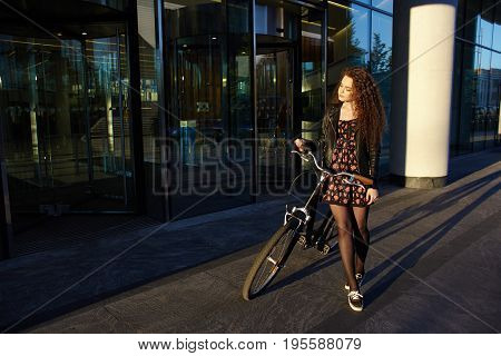 Outdoor summer shot of cute young woman wearing sneakers dress and denim jacket enjoying nice sunny evening riding retro bike. People leisure hobby activity and healthy lifestyle concept