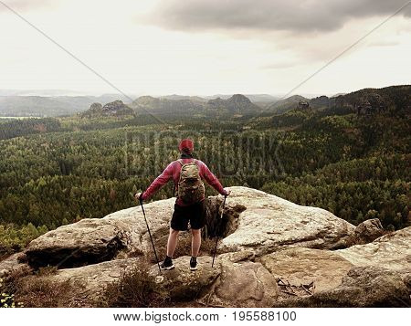 Man Hiker With Trekking Poles And Backpack On A Top Of A Mountain. Traveler With Backpack