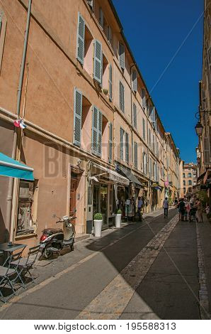 Aix-en-Provence, France - July 09, 2016. Alley with people and blue sky in Aix-en-Provence, a lively town in the French countryside. Bouches-du-Rhone department, Provence region, southeastern France