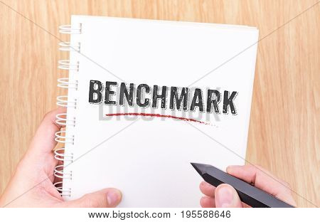 Benchmark Word On White Ring Binder Notebook With Hand Holding Pencil On Wood Table,business Concept