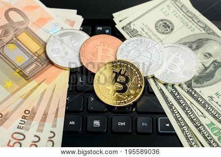 bitcoin and litecoin coins with dollars and euro banknotes on black notepad keyboard