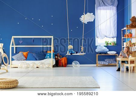 Young smiling girl drawing in colorful original decorated room