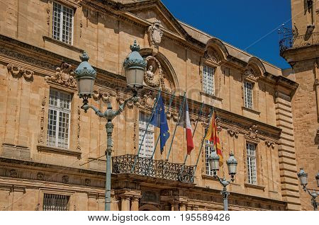 Aix-en-Provence, France - July 09, 2016. Close-up facade of the city hall with flags in Aix-en-Provence, a pleasant and vivid city in the French countryside. Provence region, southeastern France
