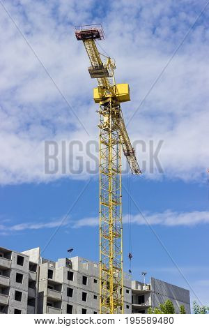 Tower crane with latticed boom on the background of the upper part of a multi-story residential building under construction and sky