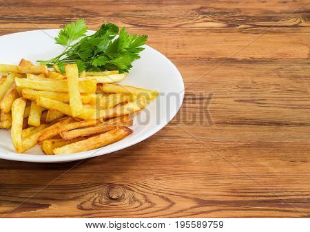 Fragment of the white dish with French fries and several twigs of parsley on a surface of old wooden planks