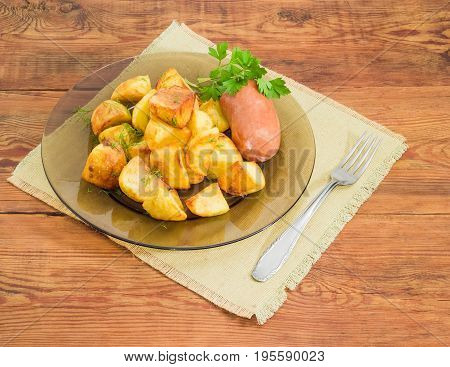 Serving of the country style fried potatoes sprinkled by chopped dill fried wieners and twig of parsley on dark glass dish and fork on textile napkin on a surface of old wooden planks