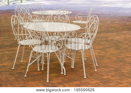 White metallic tables and chairs with openwork backs on the floor made of a brown tiles in summer cafe