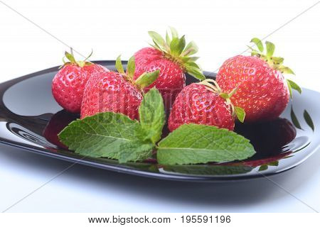 Fresh strawberries and mint leaves on black plate. Selective focus