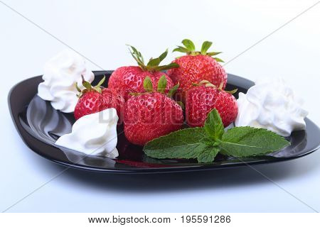 Fresh strawberries with whipped cream and mint leaves on a black plate. Selective focus