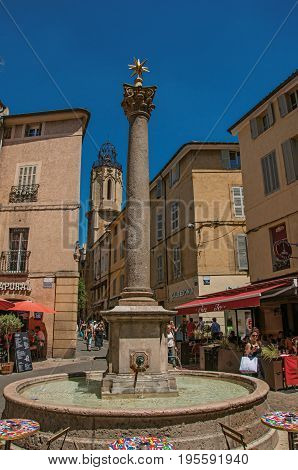 Aix-en-Provence, France - July 09, 2016. Pram with tower, people, shops and fountain in Aix-en-Provence, a pleasant and lively town in the French countryside. Provence region, southeastern France