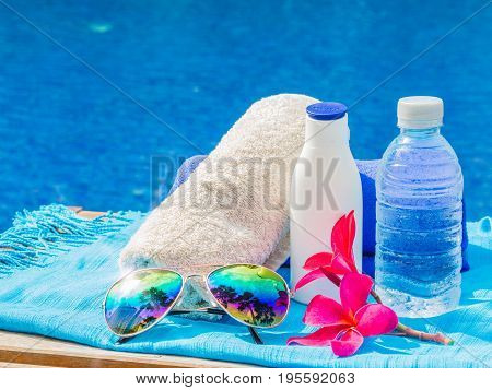 Red frangipani (plumeria) flowers sunglasses sunscreen blue and white towels at the side of swimming pool. Vacation beach summer travel concept