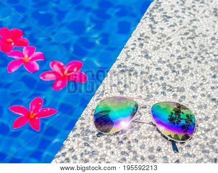 Sunglasses and red frangipani (plumeria) flowers at the side of swimming pool. Vacation beach summer travel concept
