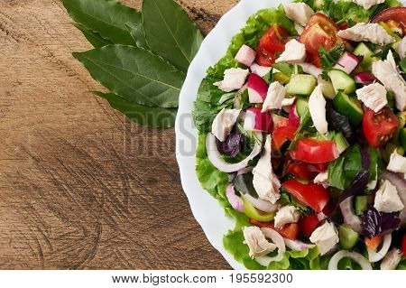Healthy salad plate with bell pepper tomatoes chicken cucumder onion and mixed greens lettuce parsley on wooden background. Food and health.