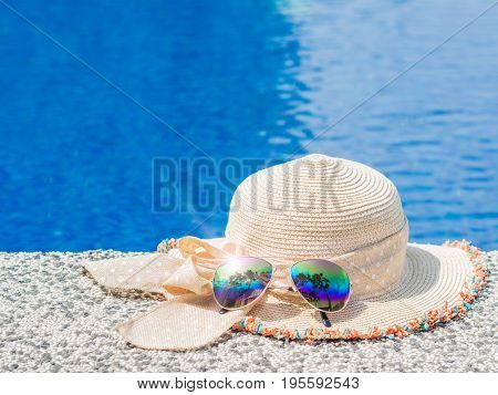 Beautiful summer hat and sunglasses at the side of swimming pool. Vacation beach summer travel concept