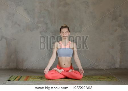 Young Woman Practicing Lotus Yoga Pose / Padmasana Against Texturized Wall / Urban Background