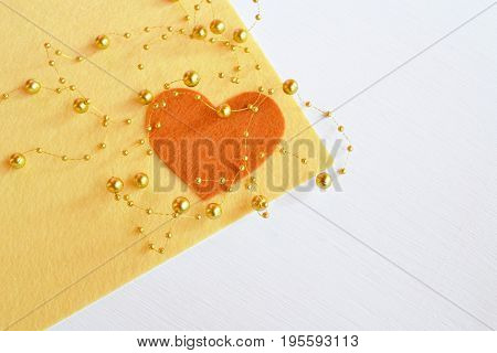 Felt heart with beads on a beige felt sheet. Heart background