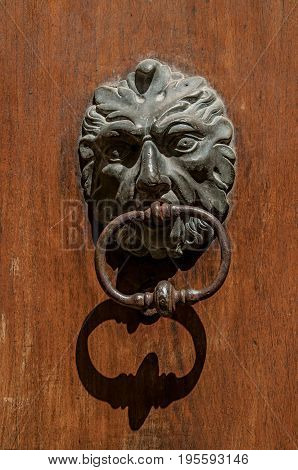 Close-up of face-shaped knocker on wooden door in Aix-en-Provence, a pleasant and lively town in the French countryside. In the Bouches-du-Rhone department, Provence region, southeastern France