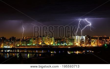 Thunderstorm in Irkutsk city with few lightnings in dark sky near Angara river