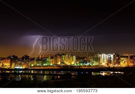Lightnings in the sky above city buildings in Irkutsk near river Angara