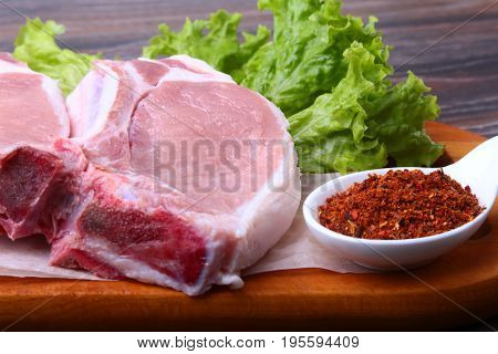 Raw pork steak with spices Leaves lettuce on wooden cutting board. Ready for cooking