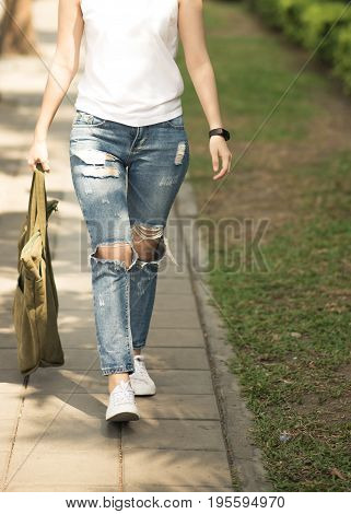 Women wear white shirts with Lack of pants Hold canvas bag Walking on the sidewalk.