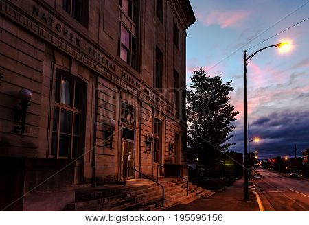 Bowling Green Kentucky USA - June 22 2017: William H. Natcher Federal Building and United States Courthouse at dusk lit by a streetlamp. It is a three-story Renaissance Revival white limestone building with a rusticated base.