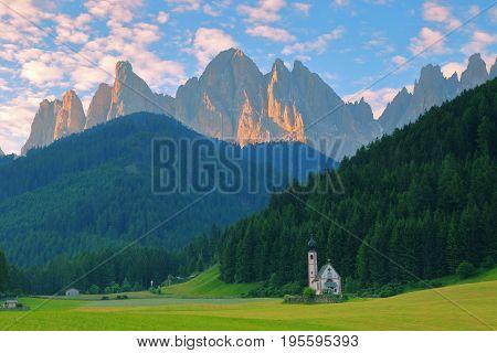 San Giovanni Church in front of dolomites mountain peaks in Santa Magdalena Italy