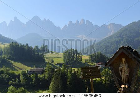 Virgin Mary statue in front of Dolomites Group, Val di Funes, Italy,
