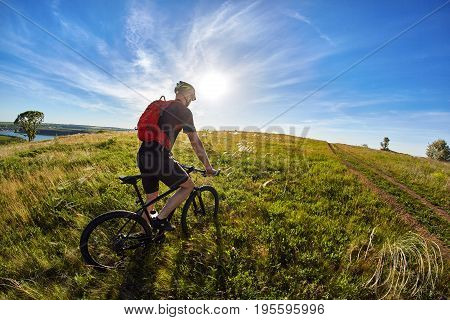 Young cyclist riding mountain bicyclist against beautiful sunset in the countryside. Sportsman dressed in the black sportwear and sporty shoes, with helmet and backpack. Horizontal photo and fisheye. Concept of the healthy lifestyle.