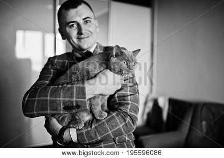 Handsome Groom Posing With A Little Cute Kitten In His Room. Black And White Photo.
