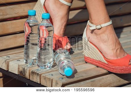 legs of a Young girl with a bottles of water. healthy lifestyle concept. girl suffering summer heat.