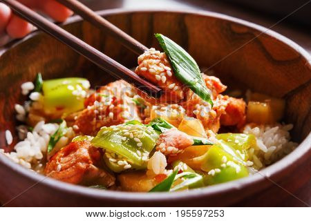Asian cuisine - rice in sauce with stir fried vegetables pineapple and salmon. Wooden bowl with chopsticks. Close up.