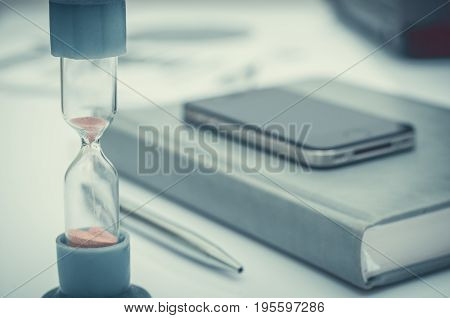 Hourglass. Businessman working in the office in the background. Concept time is money