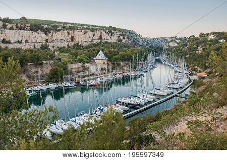 Boats anchored in a harbor inside a cliff (Calanque) near Cassis, a beautiful and sunny seaside town with harbor. Located in the Bouches-du-Rhone department, Provence region, southeastern France