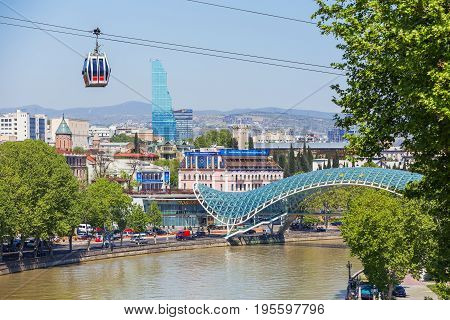 TBILISI GEORGIA - May 01 2017. Panorama view on modern landmarks - Bridge of Peace and Biltmore Hotel Tbilisi. Cable road cabin gliding over the town.