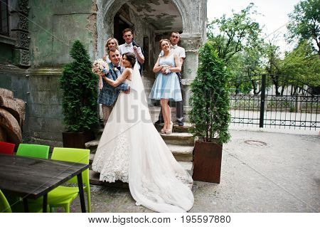 Attractive Wedding Couple And Bridesmaids With Groomsmen Are Having Fun Outdoors.