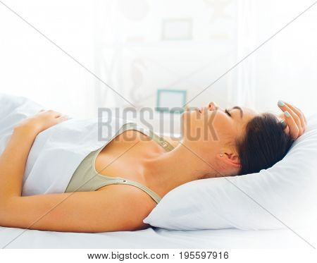 Beauty brunette girl sleeping in her comfortable bed. Beautiful lifestyle woman waking up in bed at home in the morning. Brunette female sleeps in her bedroom, resting sexy young woman