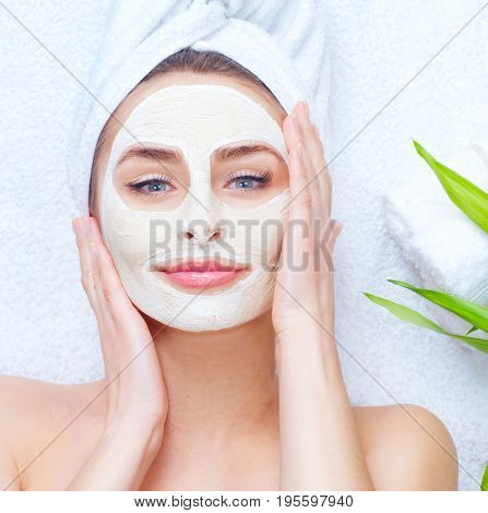 Spa Woman applying Facial clay Mask. Beauty Treatments. Close-up portrait of beautiful girl with a towel on her head applying facial mask. Skin care concept, cure, acne treatment, anti aging cosmetics