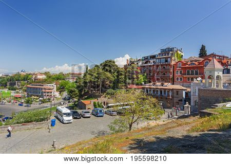 TBILISI GEORGIA - May 01 2017. Tourists walking near Tiflis Metekhi Hotel and park Rike. Panorama view on old town from Metekhi Church of the Dormition of the virgin.