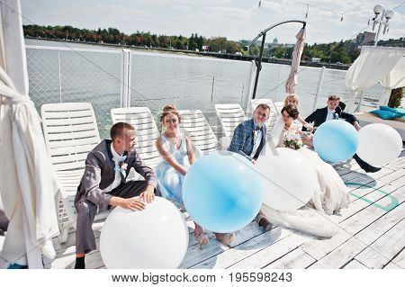 Wedding Couple, Groomsmen And Bridesmaids Having Fun With Balloons On Wharf.
