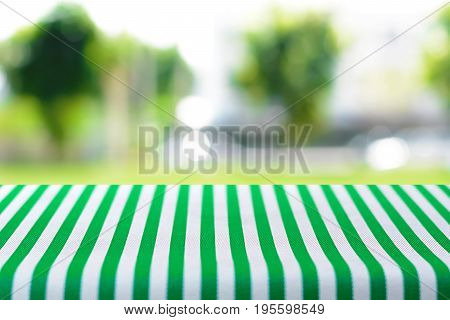Table top covered with striped tablecloth on blurred green nature background - can be used for montage or display your products