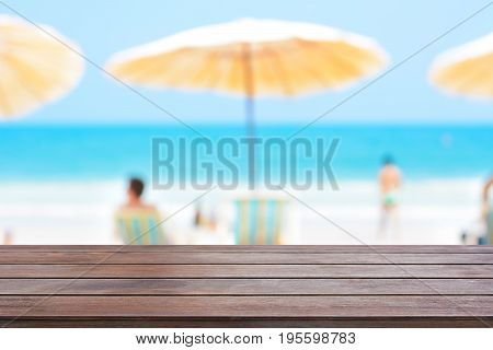 Old dark brown wood table top on blurred beach background - can be used for display or montage your products